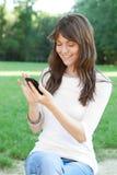 Jonge Vrouw die de Telefoon van de Cel met behulp van Royalty-vrije Stock Afbeeldingen