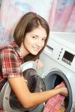 Jonge vrouw die de wasmachine laadt royalty-vrije stock fotografie
