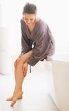 Jonge vrouw die de zachtheid van de beenhuid in badkamers controleren stock foto's