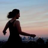 Jonge vrouw die in de zonsondergang dansen Royalty-vrije Stock Fotografie