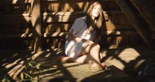 Jonge vrouw die in de zonstralen glimlachen op het hooi Houten loods 4K stock footage