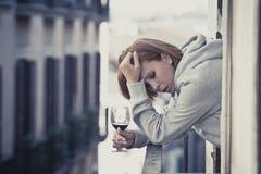 Jonge vrouw die depressie het drinken aan wijn lijden in openlucht bij het balkon stock afbeeldingen