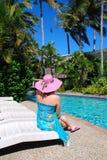 Jonge vrouw die dichtbij een zwembad situeert Royalty-vrije Stock Afbeelding