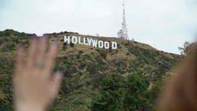 Jonge vrouw die dichtbij Hollywood-teken lopen stock video