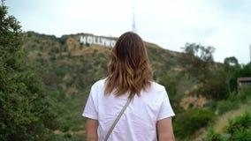 Jonge vrouw die dichtbij Hollywood-teken lopen stock footage