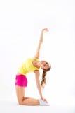 Jonge vrouw die die aerobics en uitrekken doen, op witte bac wordt geïsoleerd Stock Foto's
