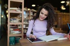 Jonge vrouw die digitale tablet in bar gebruiken stock afbeelding