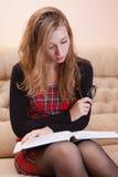 Jonge vrouw die dik boek op een bank leest Royalty-vrije Stock Foto's