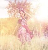 Jonge vrouw die dirndl het stellen op het gebied dragen Stock Afbeelding