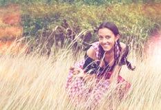 Jonge vrouw die dirndl het stellen op het gebied dragen Stock Foto's