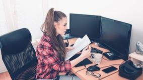Jonge vrouw die documenten vergelijken met een computer stock afbeeldingen