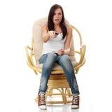 Jonge vrouw die doen schrikken op TV let - Stock Fotografie