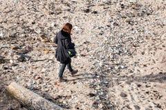 Jonge vrouw die in donkere kleding van strand genieten Royalty-vrije Stock Foto