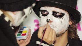 Jonge Vrouw die Donkere Make-up op Man Gezicht toepassen stock videobeelden