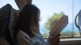 Jonge vrouw die door bus reizen en boek lezen Het meisje reist in de auto voor het venster stock video