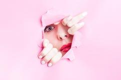 Jonge vrouw die door gescheurd roze karton kijken Royalty-vrije Stock Foto