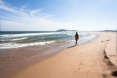 Jonge vrouw die door het lege, wilde strand tegen een blauwe hemel lopen, gele zand en overzees Brede hoek Royalty-vrije Stock Foto's
