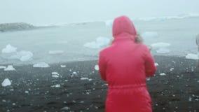 Jonge vrouw die door het vulkanische zwarte strand aan de mens in regenjas lopen die zich alleen op de kust bevinden Koude regena stock video