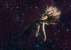 Jonge vrouw die door ruimte vallen stock foto