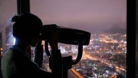 Jonge vrouw die door toeristentelescoop kijken en nachtcityscape onderzoeken stock video