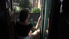 Jonge vrouw die door trein in Sri Lanka reizen, zetel, geen deuren, wildernisachtergrond stock videobeelden