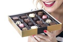 Jonge Vrouw die Doos Chocolade eten stock afbeelding