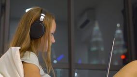 Jonge vrouw die draadloze hoofdtelefoons dragen die gebruikend een laptop zitting aan haar bed met silhouetten van skyscrappers w stock videobeelden