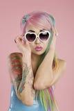 Jonge vrouw die dragend zonnebril over roze achtergrond stellen Royalty-vrije Stock Afbeelding