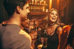 Jonge vrouw die drank hebben bij nachtclub met vrienden stock foto's