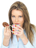 Jonge Vrouw die Drinkend Thee en Etend Koekjes of Koekje genieten van Stock Foto