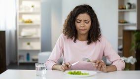 Jonge vrouw die dwingen om salade, ontevredenheid, het dieet van de gewichtscontrole te eten stock afbeeldingen