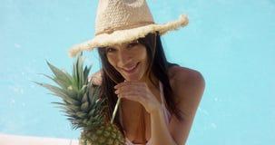 Jonge vrouw die een ananascocktail nippen stock videobeelden