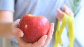 Jonge vrouw die een appel standhouden stock videobeelden