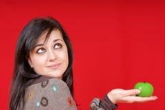 Jonge vrouw die een appelvormige kaars houdt Stock Afbeeldingen
