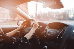 Jonge vrouw die een auto drijft stock foto