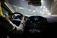 Jonge vrouw die een auto drijven bij nacht royalty-vrije stock afbeeldingen