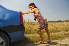 Jonge vrouw die een auto duwt stock afbeeldingen