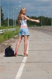 Jonge vrouw die een auto tegenhoudt. Royalty-vrije Stock Afbeelding