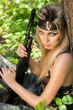 Jonge vrouw die een automatisch aanvalsgeweer houden Stock Afbeeldingen