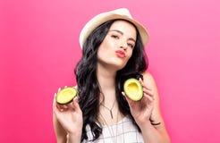 Jonge vrouw die een avocado houden Royalty-vrije Stock Afbeeldingen