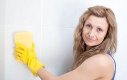 Jonge vrouw die een badkamers schoonmaakt stock afbeelding