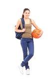Jonge vrouw die een basketbal houden Stock Afbeelding