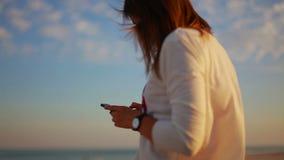 Jonge vrouw die een bericht op uw smartphone lezen bij zonsondergang op het zandige strand stock footage