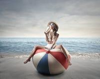 Jonge vrouw die een bikini op baloon dragen aan de overzeese kant Royalty-vrije Stock Afbeelding