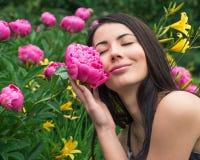 Jonge vrouw die een bloempioen ruiken stock foto