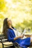 Jonge vrouw die een boek in het park leest royalty-vrije stock afbeelding