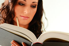 Jonge vrouw die een boek leest dat op wit wordt geïsoleerde Royalty-vrije Stock Foto's