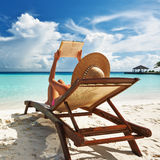 Jonge vrouw die een boek lezen bij strand Royalty-vrije Stock Afbeelding