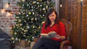 Jonge Vrouw die een Boek lezen dichtbij de Kerstboom stock videobeelden