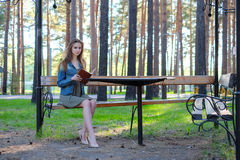 Jonge vrouw die een boek lezen en bij het park ontspannen royalty-vrije stock afbeelding
